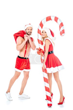 Photo for Attractive young woman with striped christmas stick and muscular shirtless man in santa hat isolated on white background - Royalty Free Image
