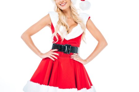 partial view of young woman in santa dress and christmas hat standing with hands on waist isolated on white background