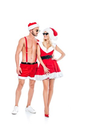 happy couple in christmas hats and sunglasses standing isolated on white background