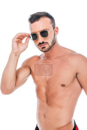 Photo for Serious muscular shirtless man adjusting sunglasses and looking at camera isolated on white background - Royalty Free Image