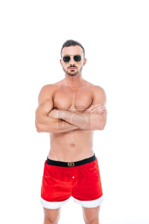 serious muscular man in christmas shorts and sunglasses standing with crossed arms isolated on white background