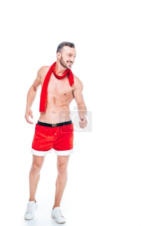happy shirtless muscular man in christmas shorts and red scarf isolated on white background
