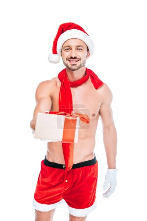 smiling shirtless muscular man in christmas hat and red scarf giving present isolated on white background
