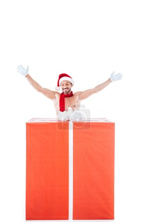 happy shirtless muscular man in christmas hat standing with raised arms near big gift box isolated on white background