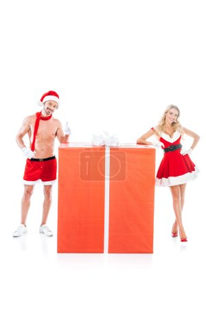 muscular shirtless man in christmas hat doing thumb up while his girlfriend standing near gift box isolated on white background