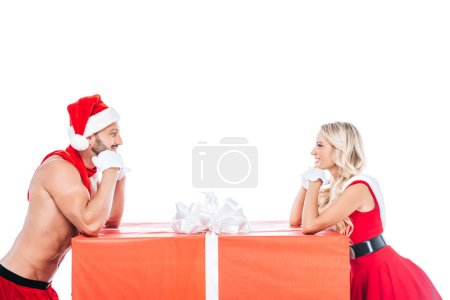 side view of dreamy couple in christmas clothes looking at each other near big gift box isolated on white background