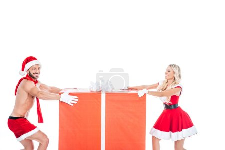 happy couple in christmas clothes pulling big gift box in different directions isolated on white background