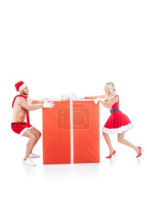 side view of happy couple in christmas clothes pulling big gift box in different directions isolated on white background