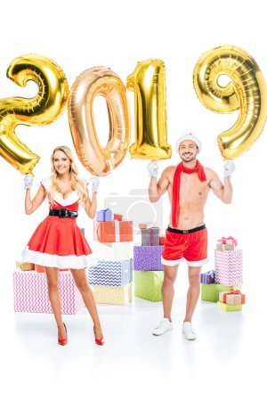 happy young woman in santa dress and her muscular shirtless boyfriend in christmas hat holding sign 2019 made of golden air balloons in front of pile of gift boxes isolated on white background