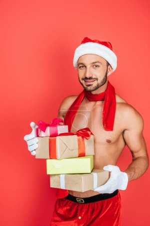 happy muscular shirtless man in christmas hat and red scarf holding pile of gift boxes isolated on red background