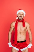 smiling muscular shirtless man in christmas hat and red scarf touching own shorts isolated on red background