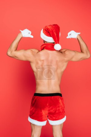 rear view of muscular shirtless man in christmas hat and shorts showing muscles isolated on red background