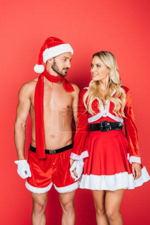 muscular shirtless man in christmas hat and red scarf and his smiling girlfriend looking at each other isolated on red background