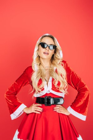 sexy santa girl in christmas dress and sunglasses standing with hands on waist isolated on red background