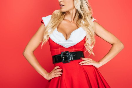 partial view of sexy santa girl in christmas dress standing waith hands on waist isolated on red background