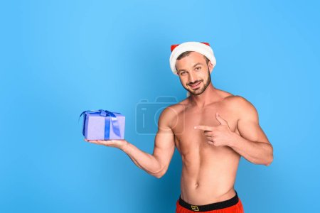 handsome shirtless muscular man in christmas hat pointing at gift box isolated on blue background