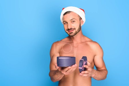 portrait of shirtless muscular man in christmas hat holding gift box isolated on blue background