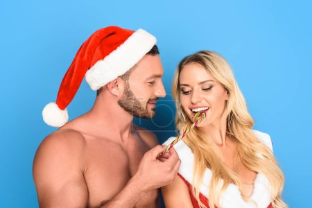 muscular shirtless man in christmas hat feeding girlfriend by striped christmas stick isolated on white background