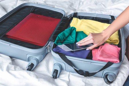 Photo pour Plan recadré de femme valise d'emballage pour le voyage sur le lit - image libre de droit