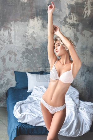 attractive young woman in stylish underwear stretching in loft bedroom in morning