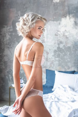 Photo for Seductive young woman in stylish underwear standing in loft bedroom and looking away - Royalty Free Image