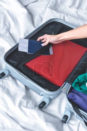 cropped shot of woman packing luggage for trip on bed