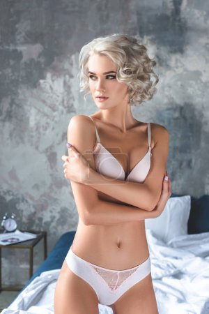 attractive young woman in stylish underwear standing in loft bedroom and looking away