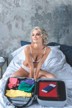 excited young woman sitting on bed in underwear while packing luggage for trip
