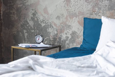Photo for Messy bed in loft bedroom with vintage alarm clock and newspaper on bedside table - Royalty Free Image
