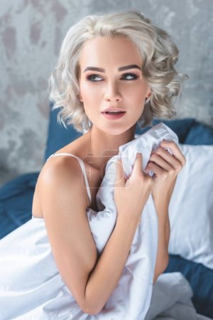 Photo for Sexy young woman sitting on bed in underwear while covering with blanket and looking away - Royalty Free Image