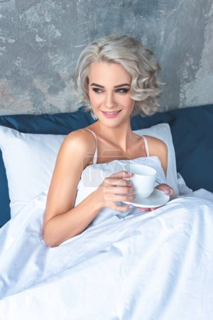 happy young woman lying in bed with cup of coffee in morning