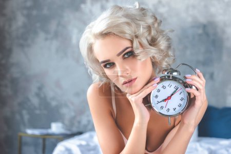 close-up portrait of attractive young woman holding vintage alarm clock and looking at camera