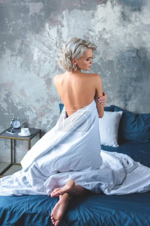 rear view of seductive naked young woman standing on knees in bed and covering her body with blanket