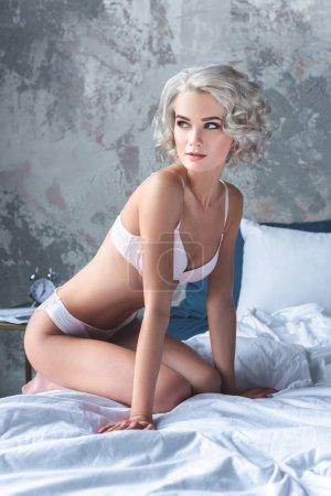 Photo pour Belle jeune femme avec des cheveux bouclés en sous-vêtements assis sur le lit et la recherche. - image libre de droit