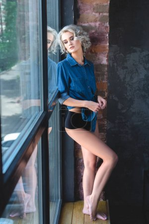 attractive young woman in denim shirt and underwear standing near large loft window