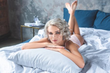 attractive young woman in underwear lying in bed and looking at camera