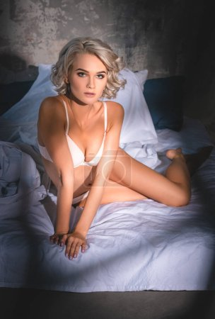 attractive young woman in underwear lying in bed under sunset rays and looking at camera
