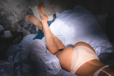 cropped shot of woman in underwear lying in bed under sunset rays