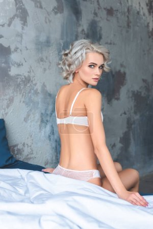 Photo for Beautiful young woman with curly hair sitting on bed in underwear - Royalty Free Image