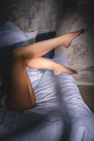 cropped shot of seductive woman in underwear lying in bed under sunset rays