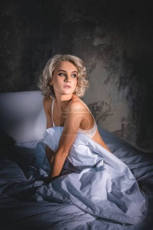 Photo for Attractive young woman in underwear sitting in bed under sunset rays and looking away - Royalty Free Image