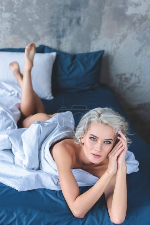 seductive naked young woman lying in bed under blanket and looking at camera
