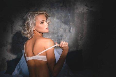 Photo pour Attrayant jeune femme en sous-vêtements assis dans le lit et enlever soutien-gorge sous les rayons du coucher du soleil - image libre de droit