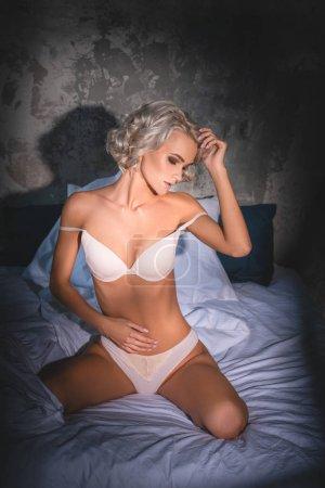 Photo pour Séduisante jeune femme en sous-vêtements, assis dans son lit sous les rayons du coucher du soleil - image libre de droit