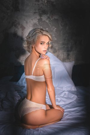 attractive young woman in underwear sitting in bed and looking at camera under sunset rays