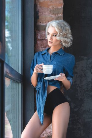 seductive young woman in denim shirt and panties with cup of coffee looking through large window