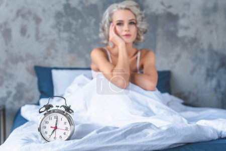 attractive young woman sitting in bed covered with white blanket with vintage alarm clock lying on foreground