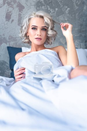 beautiful young woman lying in bed covered with white blanket