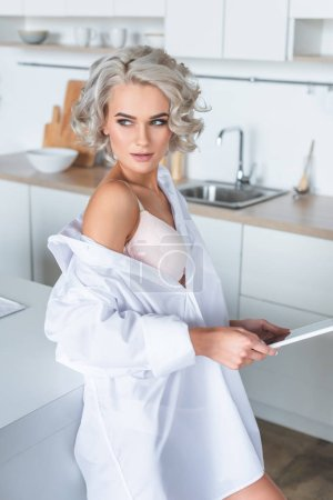 seductive young woman in white shirt holding tablet and looking away at kitchen in morning