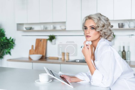 attractive young woman in white shirt holding tablet and looking away at kitchen in morning